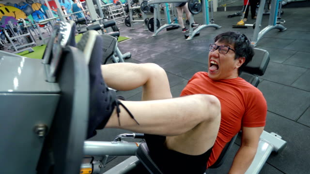 asian large build man exercising his leg with extremely painful face. - leg press stock videos & royalty-free footage
