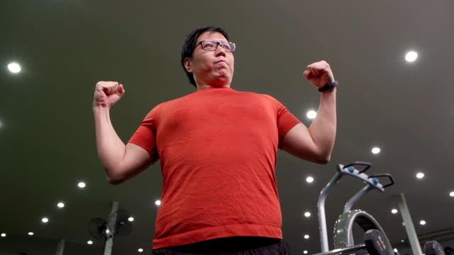 vídeos y material grabado en eventos de stock de asiático grande construir hombre flexionando sus músculos en el gimnasio. - piel grasa