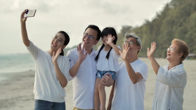 asian large family making a selfie or video call to connect with relatives on sand beach during covid-19 lockdown.social distancing,technology,elderly,vacations,relationship,retirement,healthycare and medicine,south east and east asia: asia: generational - east asian ethnicity video stock e b–roll