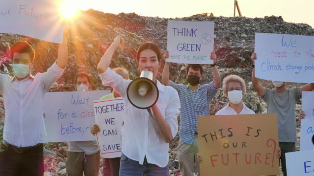 asian leadership women shouting on megaphone of group asian volunteers of different age on a huge garbage dump from landfill site in asia and holding posters for environmental movement activists fighting for nature.volunteerism, charity, cleaning, ecology - medical leadership stock videos & royalty-free footage