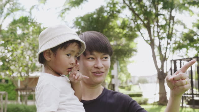 asian lesbian and little baby boy enjoy nature at garden. - intersex stock videos and b-roll footage