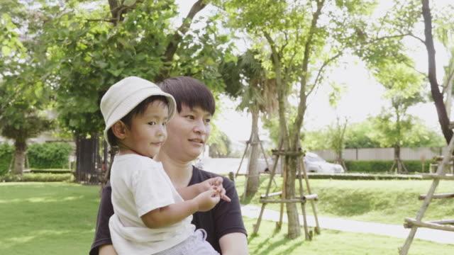 Asian lesbian and little baby boy enjoy nature at garden.