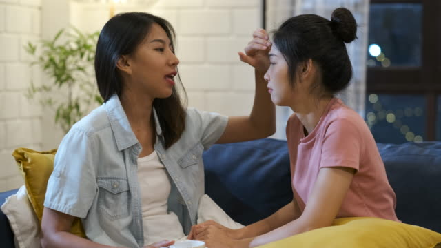 vídeos de stock e filmes b-roll de asian lesbian couple comforting girlfriend when she sad with love and care in night time at home - consolar