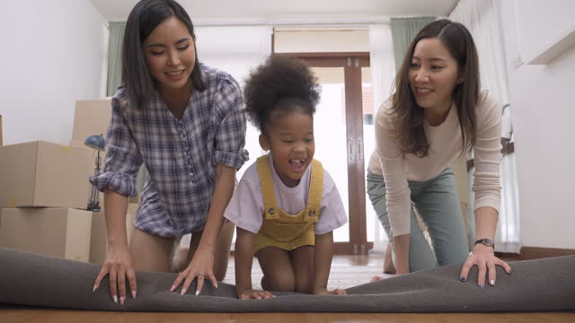 asian lgbtq  woman couple with an adopted child, african teenager girls lay the carpet down in a new house among stacked paper box on moving day, helping together to moving in a warm home with smiling, feeling happy, positive emotion. - lesbian stock videos & royalty-free footage