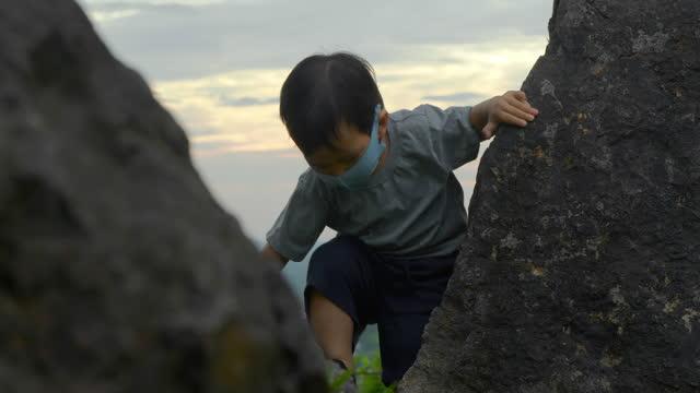 vidéos et rushes de asiatique petit garçon de 14 mois portant un masque protecteur a essayé d'escalader tout en apprenant dans la forêt pendant la distanciation sociale pour empêcher des épidémies de coronavirus ou de covid-19.masques et revêtements de visage (non ca - new age concept