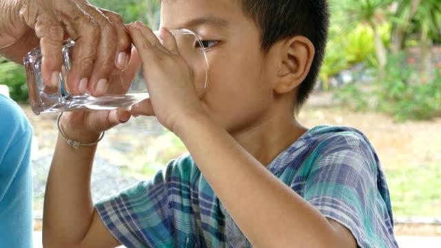 アジアの小さな男の子は、自宅でガラスから水を飲みます - 男の子点の映像素材/bロール
