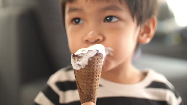 asian little boy eating ice cream at home - confectionery stock videos & royalty-free footage