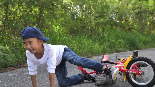 asian little boy learn to ride and falling a bicycle in garden, learn to ride a bike - boys stock videos & royalty-free footage