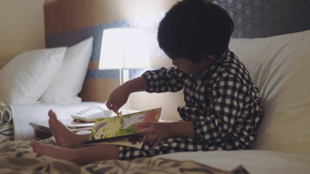 asian little boy reading a book on the bed at night. - reading stock videos & royalty-free footage