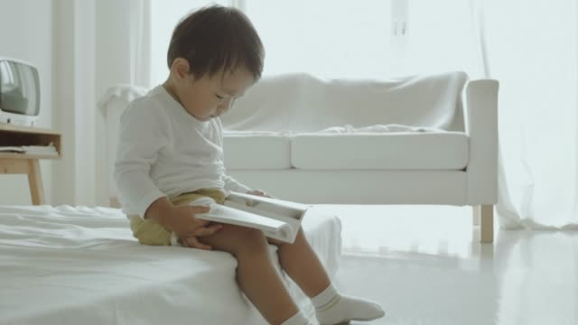 Asian little boy reading a book on the bed