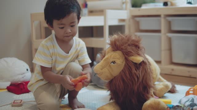 vídeos y material grabado en eventos de stock de niño pequeño asiático jugando en casa - juguete