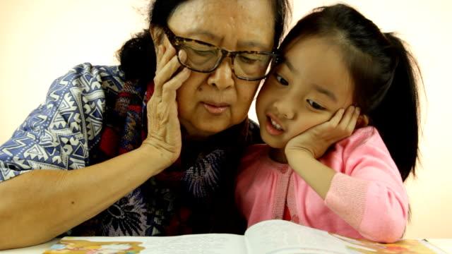 Asian little girl and grandma reading book