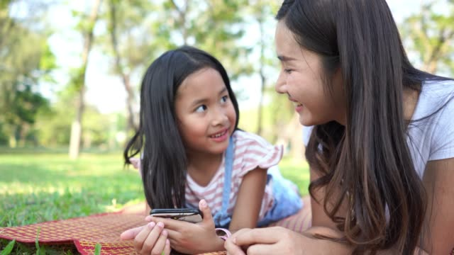 vídeos de stock e filmes b-roll de asian little girl and young mother using mobile phone for e-learning in garden - professora
