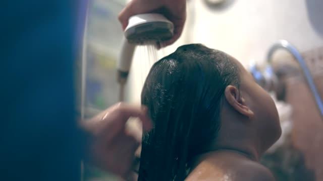 vídeos de stock e filmes b-roll de asian little girl bathing and washing hair by her mother - casa de banho doméstica