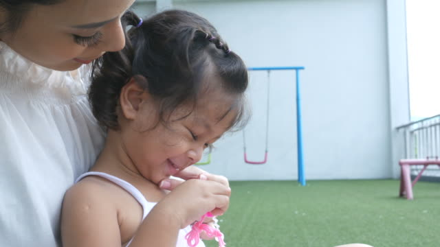 Asian little girl blows bubbles