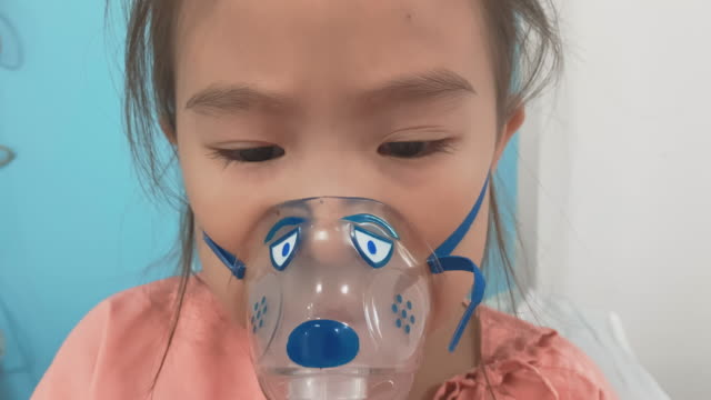 asian little girl breathes in the inhaler, inhalation mask on the face of the patient  in the hospital. - medical occupation stock videos & royalty-free footage