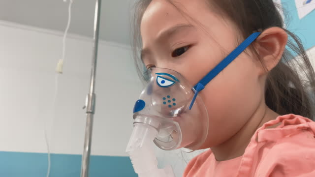 asian little girl breathes in the inhaler, inhalation mask on the face of the patient  in the hospital. - inhaling stock videos & royalty-free footage