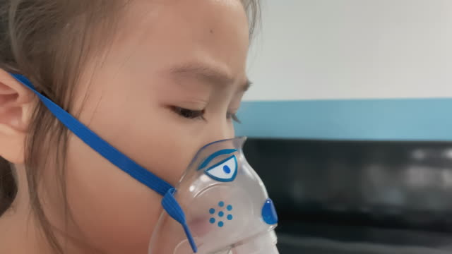 asian little girl breathes in the inhaler, inhalation mask on the face of the patient  in the hospital. - trachea stock videos & royalty-free footage