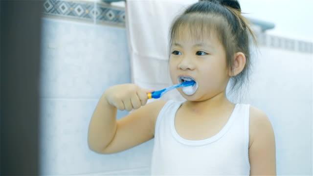 stockvideo's en b-roll-footage met aziatische meisje tandenpoetsen in de badkamer - tanden op elkaar klemmen