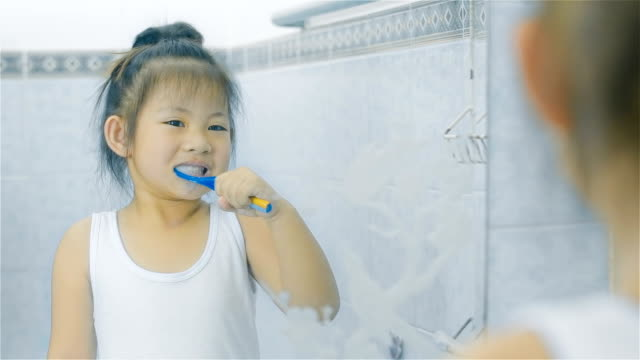 Asian little girl brushing teeth in bathroom