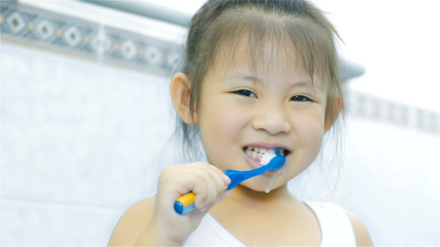 asian little girl brushing teeth in bathroom - toothpaste stock videos and b-roll footage