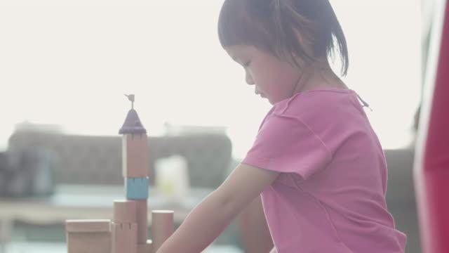 アジアの小さな女の子建物の木製のブロック