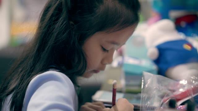 鉛筆で絵を描くアジアの小さな女の子 - 鉛筆点の映像素材/bロール