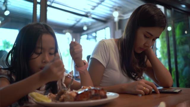 vídeos y material grabado en eventos de stock de asiática niña comiendo comida, madre usando el teléfono - nativo digital