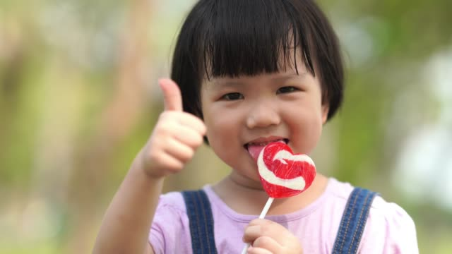 asian little girl eating lollipop , thumbs up - lollipop stock videos & royalty-free footage