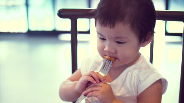 Asian Little Girl Eating Sausage In Breakfast