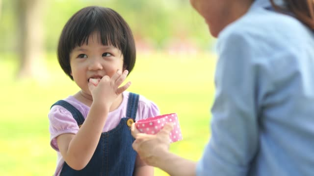 asian little girl eating sweet food from pink heart box - marshmallow video stock e b–roll