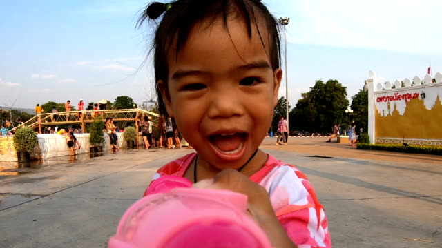 asian little girl is playing a water gun in the songkran festival of thailand. - water pistol stock videos & royalty-free footage