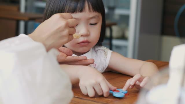 vídeos de stock, filmes e b-roll de menina asiática está jogando o brinquedo que ela não quer comer, enquanto a mãe tenta comer comida - comida de bebê