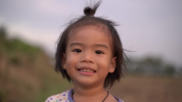 asian little girl is smiling happily. - headshot stock videos & royalty-free footage
