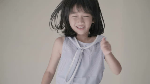 vídeos de stock e filmes b-roll de asian little girl jumping excited on the bed,slow motion. - parede