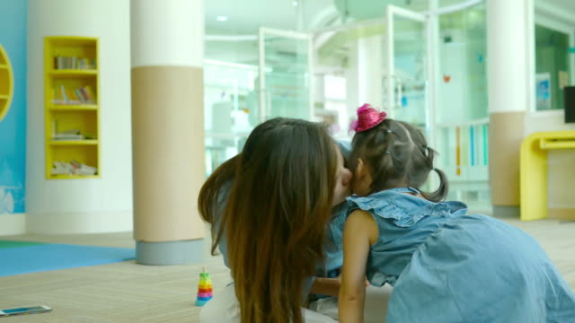 Asian little girl learning in library , kissing