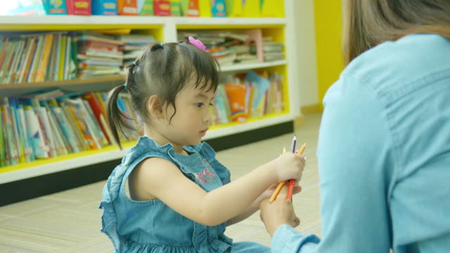 Asian little girl learning in library