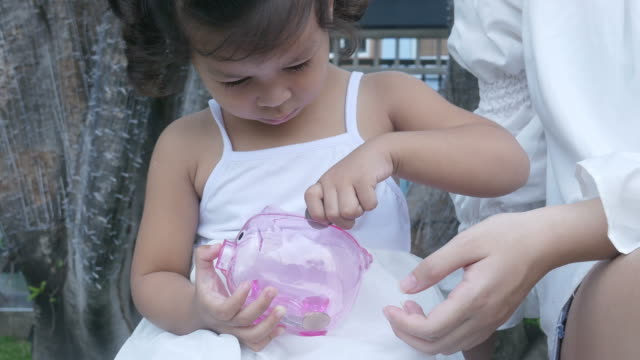 asian little girl learning to saving money - contento video stock e b–roll
