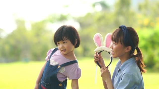 Asiatisches Mädchen Lernen mit jungen Lehrern im Garten, Ostertag-Konzept