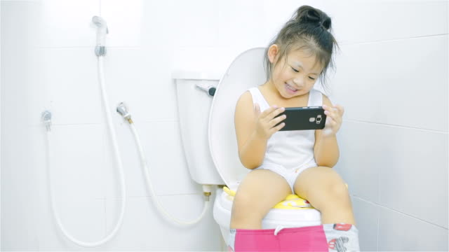 asian little girl looking at smart phone and sitting on a toilet bowl in bathroom - toilet stock videos and b-roll footage