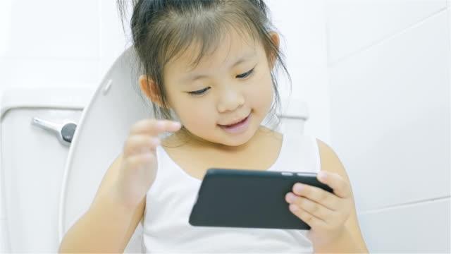 kleine asiatin smartphone betrachten und sitzen auf einer toilette im badezimmer - kind pinkelt stock-videos und b-roll-filmmaterial