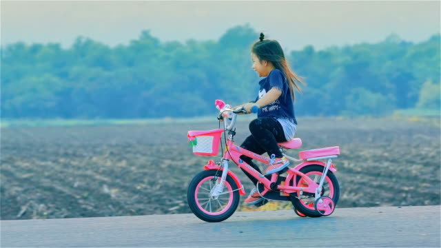 asian little girl on cycle ride in countryside - tricycle stock videos & royalty-free footage