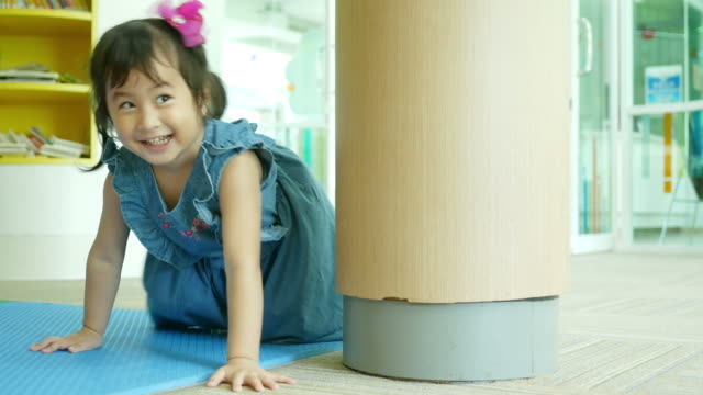 Asian little girl playing and learning in library