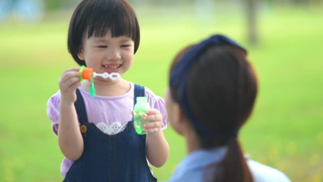 Asiatisches Mädchen spielt Blase mit jungen Lehrern im Garten