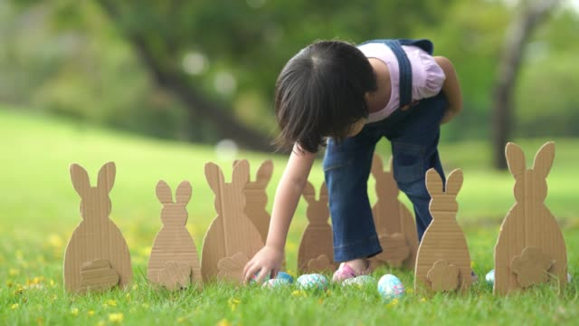 Asiatisches Mädchen, das im Garten spielt, Ostertag-Konzept