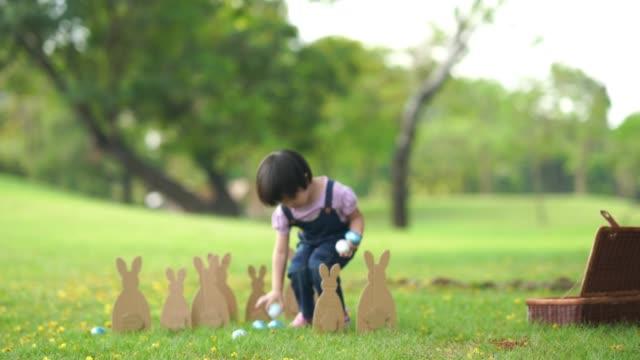 asiatisk liten flicka som leker i trädgården, påsk dagen koncept - påsk bildbanksvideor och videomaterial från bakom kulisserna