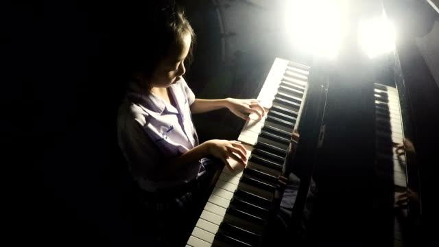 Asian little girl playing piano