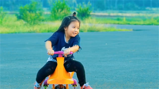 asian little girl playing swing car in countryside - tricycle stock videos & royalty-free footage