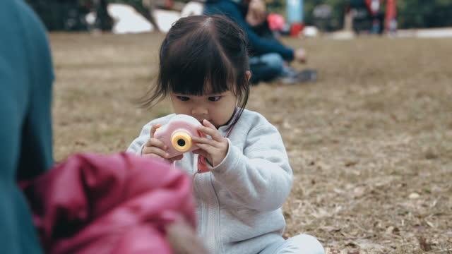 asiatische kleine mädchen spielen mit spielzeug-kamera im park - vorstellungskraft stock-videos und b-roll-filmmaterial