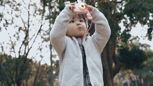 vídeos y material grabado en eventos de stock de niña asiática jugando con la cámara de juguete en el parque - niñas